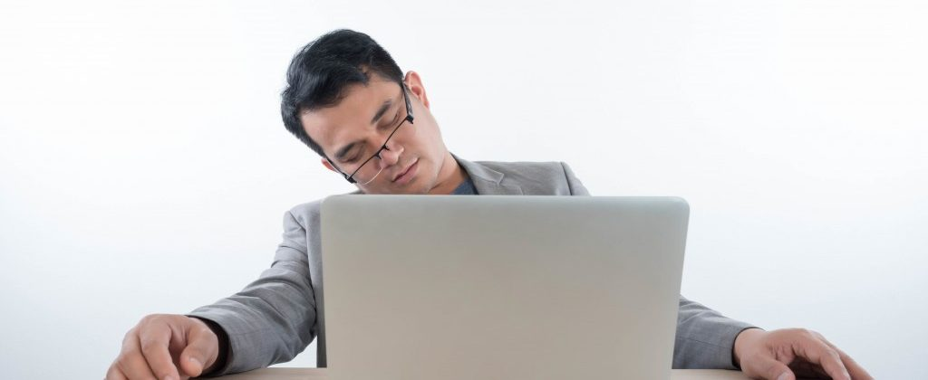 Man sleeping in the front of his laptop