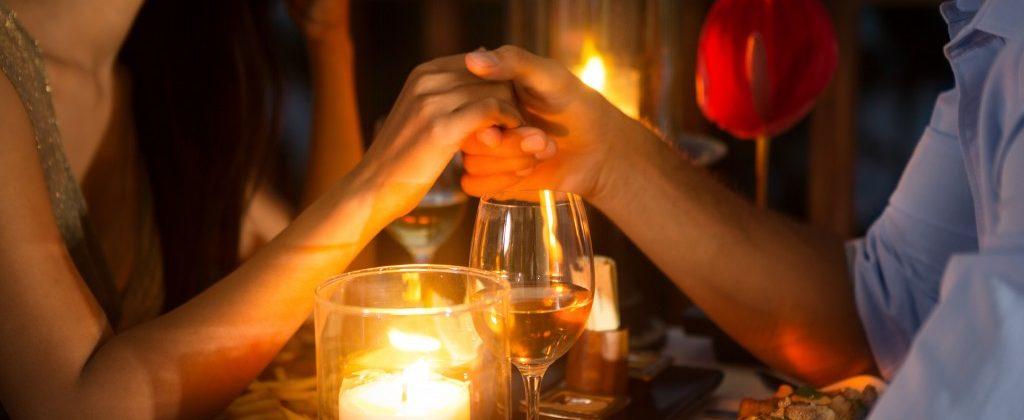a couple on a honeymooon having a candle light dinner